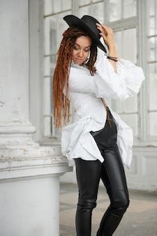 古い宮殿のフォントでポーズをとって、白いシャツ、黒い革の帽子とズボンに身を包んだドレッドヘアのファッショナブルな女の子