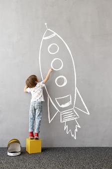 큰 꿈! 행복한 아이가 벽에 분필 로켓을 그립니다.