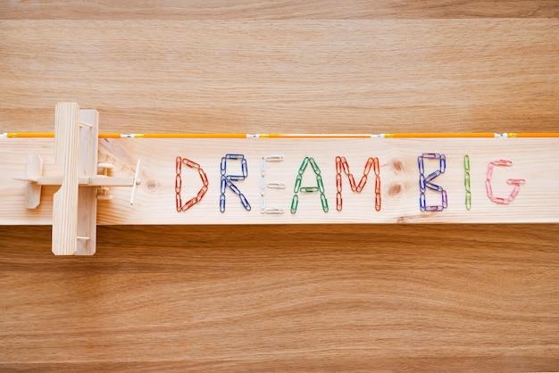 큰 꿈을 꾸세요. 화려한 스테이플과 나뭇결 위에 놓인 나무 비행기로 만든 꿈의 큰 텍스트의 상위 뷰