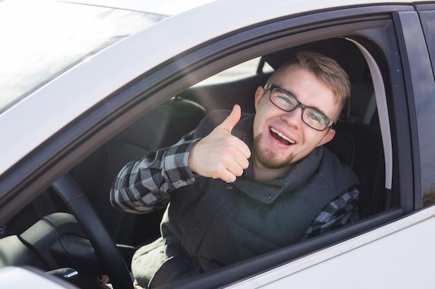 Мечты сбываются. веселый случайный парень улыбается, счастливо показывает палец вверх, сидя в большой белой машине.