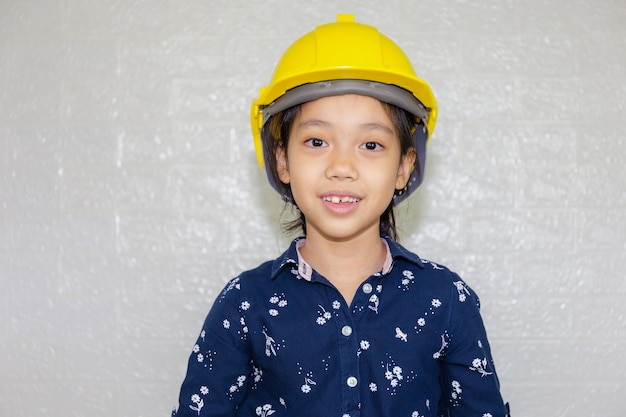 Dream career concept, portrait of happy engineer kid in hard hat looking at camera on blurred background