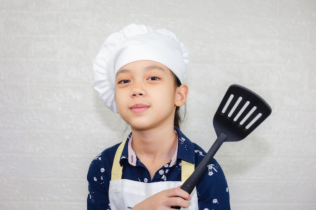 Dream careers concept, portrait of happy kid chef looking at camera with blurred background