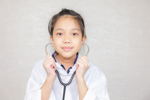 Dream careers concept, portrait of happy kid in doctor coat with stethoscope blurred background