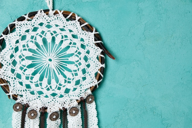 Dream catcher on aquamarine wall background