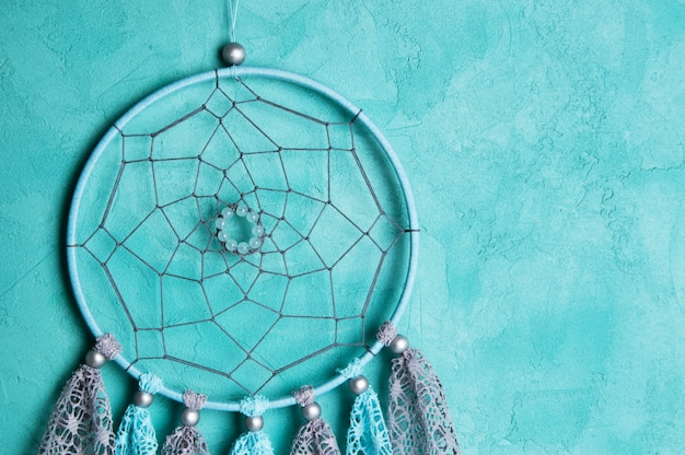 Dream catcher on aquamarine wall