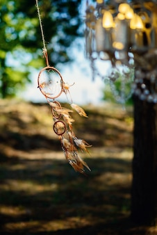 A dream catcher develops in the wind in a forest.