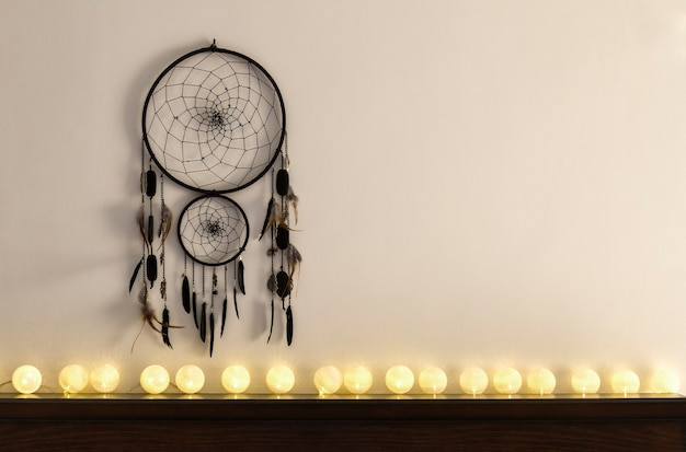 Dream catcher hanging on the wall with white cotton ball string lights