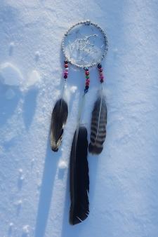 눈 배경에 꿈 포 수입니다. 깃털과 화려한 구슬로 만든 수제 장식.
