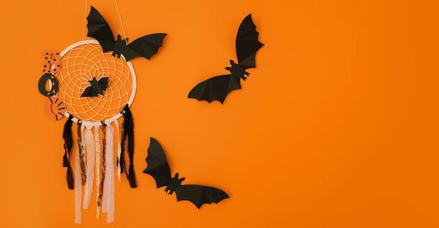 Ловец снов со словом «бу» и летучими мышами на оранжевом студийном фоне - это концепция хэллоуина