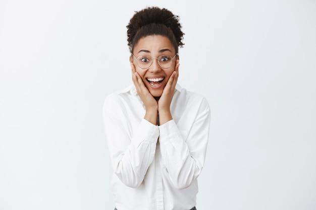 夢叶う。頬と手をつないで驚きと幸福から笑みを浮かべて、メガネと黒い肌の白いシャツを着た幸せで楽しい魅力的な女性起業家を驚かせた