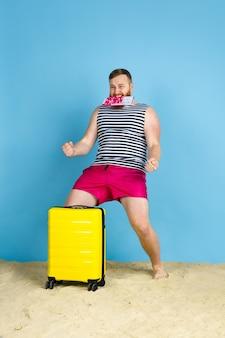 Il sogno diventa realtà. felice giovane uomo con borsa preparata per viaggiare su sfondo blu studio. concetto di emozioni umane, espressione facciale, vacanze estive, fine settimana. estate, mare, oceano, alcol.
