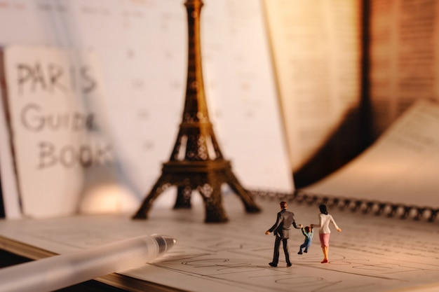 Dream destination for vacation. travel in paris, france. a miniature tourist family walking at the eiffel tower and calendar. warm tone. vintage style