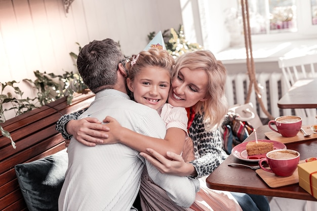 꿈의 가족. 그녀의 부모를 포옹하는 동안 웃 고 긍정적 인 예쁜 여자