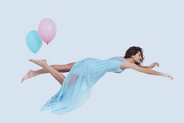Мечта летать. студийный снимок привлекательной молодой женщины в элегантном платье с вытянутыми руками на сером фоне