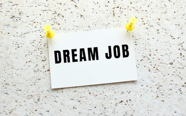 Dream job은 버튼이 있는 흰색 질감의 벽에 부착된 카드에 쓰여 있습니다. 사무실 알림입니다. 비즈니스 개념입니다.