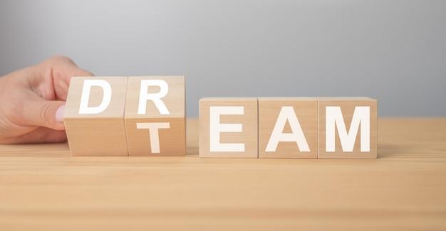 木製の立方体の夢のチーム。手はサイコロを回し、夢という言葉をチームに変えます。ドリームチームメッセージ。ビジネスと夢のチームのコンセプト、コピースペース
