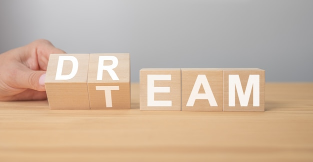 Dream team on wooden cubes. hand is turning a dice and changes the word dream to team. dream team message. business and dream team concept, copy space