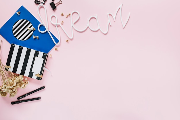 Dream text with stationery and flowers on pink backdrop