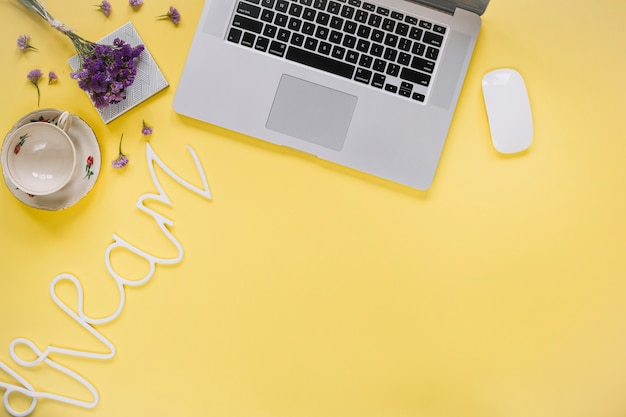 Dream word near laptop and empty cup on yellow surface