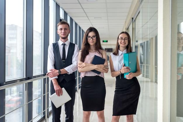 현대 사무실 복도에서 서류 작업을 논의하는 세 명의 전문 사업가로 구성된 꿈의 젊은 팀