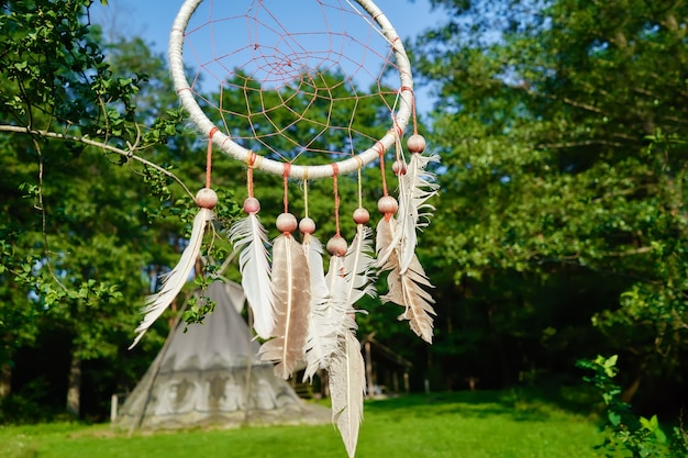 Dreamcatcher on the background of an indian village of wigwams.