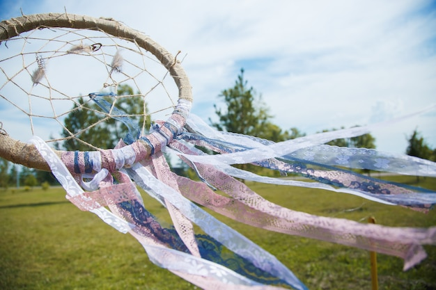 Dreamcatcher close up on a background of green grass and blue sky