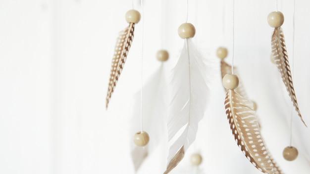 ドリームキャッチャー。羽飾り。白い背景の上の羽