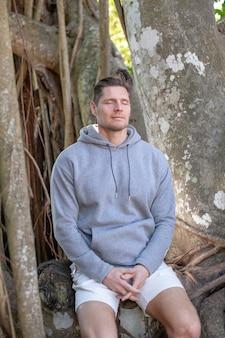 나무 근처에 앉아 있는 몽상가 남자 명상을 하는 눈을 감고 있는 남자