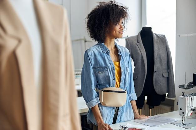 夢のようなアフリカ系アメリカ人の女性の仕立て屋は、現代的なワークショップのテーブルに立っています