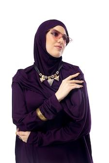 꿈결 같은. 광고용 카피스페이스가 있는 스튜디오 배경에서 세련된 히잡을 쓰고 포즈를 취하는 아름다운 아랍 여성. 패션, 뷰티, 스타일 컨셉입니다. 트렌디한 메이크업, 매니큐어, 액세서리를 갖춘 여성 모델.