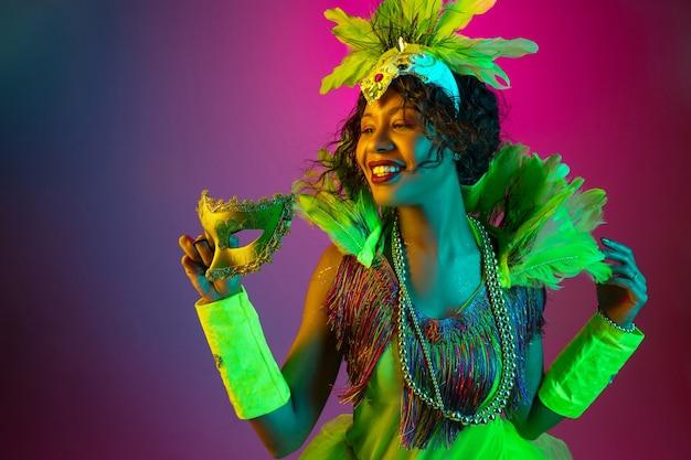 Мечтательный. красивая молодая женщина в карнавале, стильный маскарадный костюм с перьями, танцующими на градиентном фоне в неоне. концепция празднования праздников, праздничного времени, танцев, вечеринок, веселья.