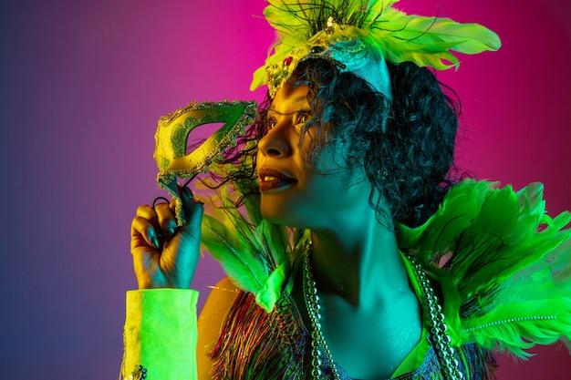 夢のような。カーニバルの美しい若い女性、ネオンのグラデーションの壁に羽が踊るスタイリッシュな仮面舞踏会の衣装。休日のお祝い、お祭りの時間、ダンス、パーティー、楽しんでの概念。