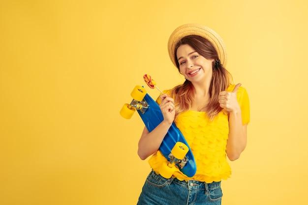 Dreamful, 스케이트를 들고 있습니다. 노란색 스튜디오 배경에 백인 여자의 초상화입니다. 모자에 아름 다운 여성 모델입니다. 인간의 감정, 표정, 판매, 광고의 개념. 여름철, 여행, 리조트.