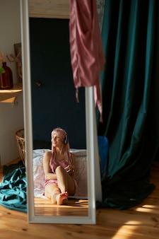 夢のようなピンクの髪の女性が寝室の大きな鏡に映る音楽を聴く