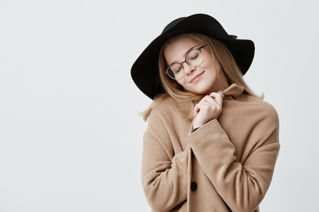 Dreamful positive female in retro outfit, wraps in coat, stands  with closed eyes, imagines something pleasant, tries to relax. positive human emotions and feelings concept