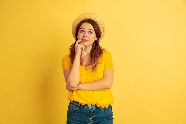 夢のような、思慮深い。黄色のスタジオで白人女性の肖像画