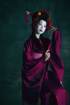 Dreamful. young japanese woman as geisha isolated on dark green wall. retro style, comparison of eras concept. beautiful female model like bright historical character, old-fashioned.