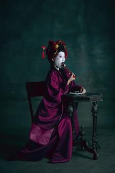 夢のような。濃い緑の壁に隔離された芸者としての若い日本人女性。レトロなスタイル、時代のコンセプトの比較。昔ながらの明るい歴史的キャラクターのような美しい女性モデル。