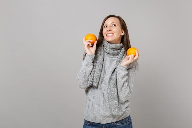 Мечтательная молодая женщина в сером шарфе свитера, глядя вверх, держа апельсины, изолированные на сером фоне в студии. люди здорового образа жизни моды искренние эмоции, концепция холодного сезона. копируйте пространство для копирования.