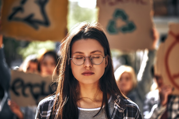 Молодая женщина в очках с закрытыми глазами мечтает о чистой земле, стоя на открытом воздухе в