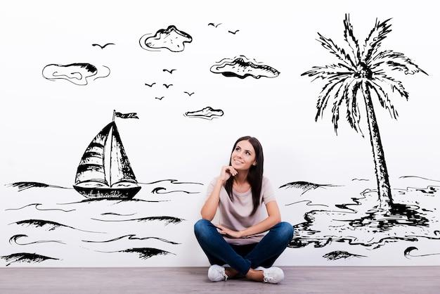 휴가에 대한 꿈. 배경에 삽화가 있는 바닥에 앉아 웃고 있는 쾌활한 젊은 여성