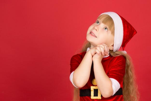 큰 꿈. 산타 클로스 옷을 입고 명랑 소녀는 꿈꾸는 찾고 측면에 copyspace 웃는