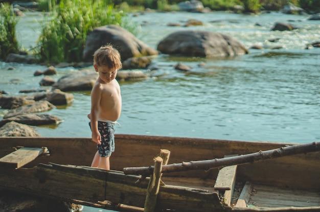 Мечтательный мальчик в старой лодке на берегу озера. милый маленький мальчик, сидящий в старой деревянной лодке на природе.