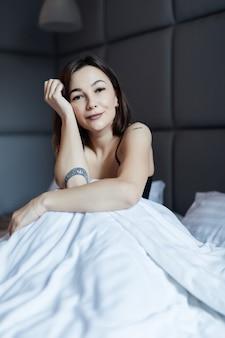 Мечтает брюнетка на белой кровати в мягком утреннем свете под одеялом
