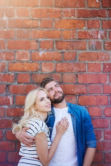 Dreaming couple standing next to brick wall