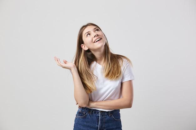 白いtシャツとジーンズに身を包んだ夢の少女は、スタジオの白い背景にあります。