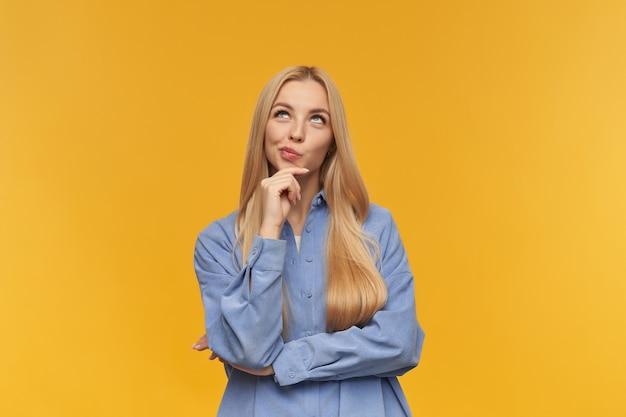 Ragazza di sogno, donna dall'aspetto felice con i capelli lunghi biondi. indossare la maglietta blu. concetto di persone ed emozione. toccandole il mento e le labbra increspate. guardando in copia spazio, isolato su sfondo arancione