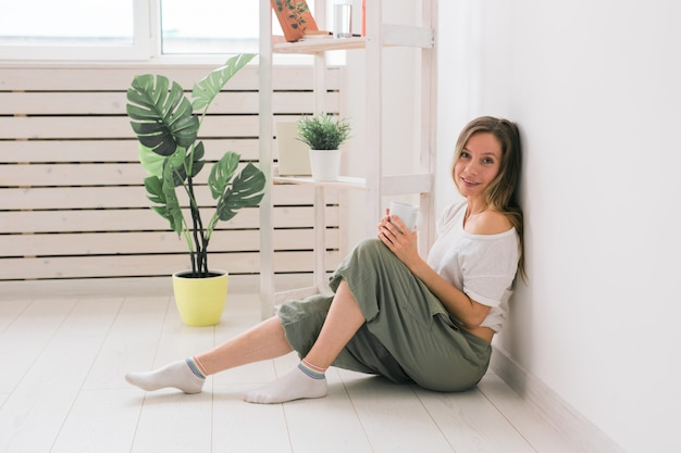 Dreaming girl sitting on floor at home and drink tea from cup