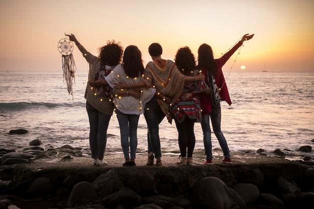 女性の友人のグループが夕日を見て一緒に抱き合って夢のようなイメージ