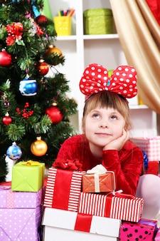 お祝いに飾られた部屋で贈り物に囲まれた赤いドレスを着た夢の少女